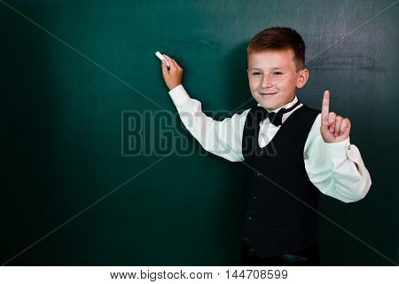 Little schoolboy holding thumb up writing on the blackboard with chalk