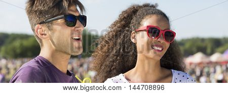 Closer shot of young man's and woman's faces with the hipster sunglasses