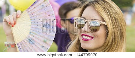 Closer shot of young blonde with sunglasses and a fan in her hand