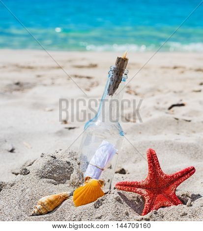 close up of a bottle with message on the sand