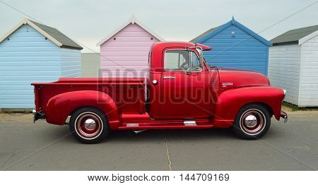 FELIXSTOWE, SUFFOLK, ENGLAND - AUGUST 27, 2016: Classic Red  Chevrolet 3100 pickup truck on seafront promenade in front of beach huts.