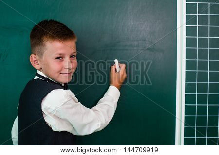 Little smiling schoolboy writing on the blackboard with chalk