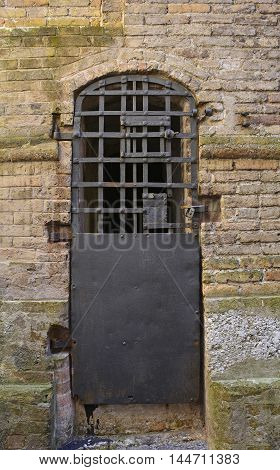 An old metal security door down a Pordenone back street in Friuli Venezia Giulia north east Italy.