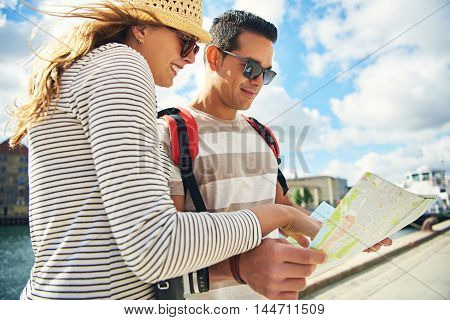 Low angle view of an attractive young tourist couple looking at a map outdoors in the summer sunshine with happy smiles
