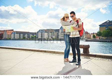 Trendy young backpackers consulting a map together on vacation as they stand on a waterfront promenade overlooking an old town