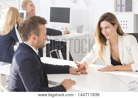 Work open space area with young woman flirting with her employee