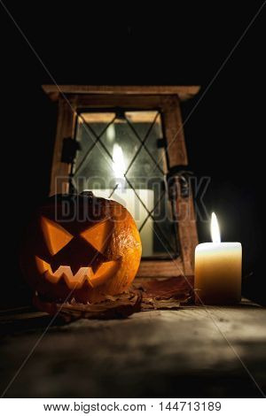 Halloween pumpkin head, lantern and candle on wooden table over black background