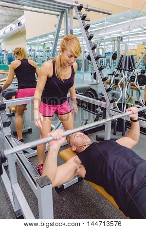 Woman personal trainer screaming to muscle man in a bench press training with barbell on fitness center. Motivation in training concept.