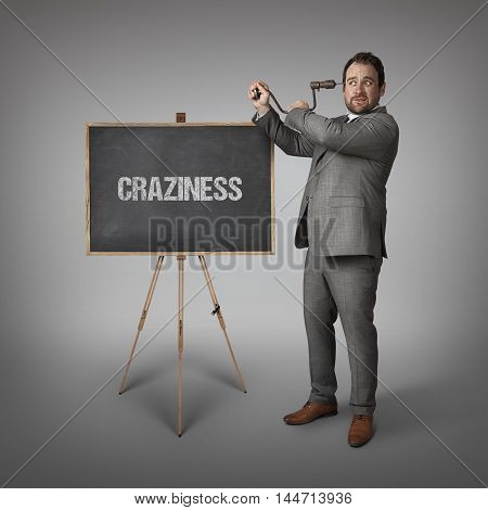Craziness text on blackboard with businessman drilling his head