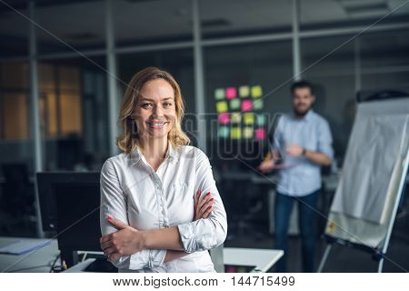 Attractive businesswoman feeling confident with crossed arms.