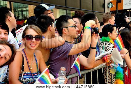 New York City - June 29 2014: Spectators watching and taking photos of the 2014 Gay Pride Parade on Fifth Avenue