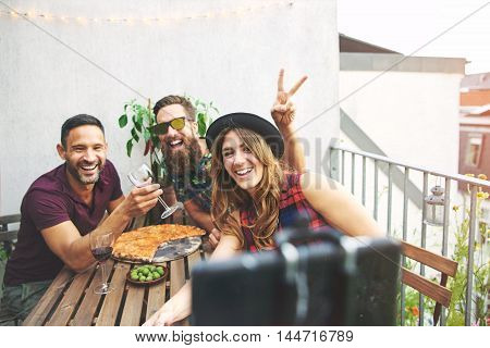 Man using rabbit ears gesture over head of friend in hat at table while eating pizza and drinking wine