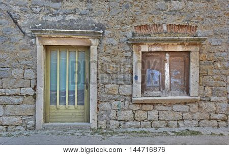 A door and window in an old historic building in the small town of Skradin on the coast of the Sibenik-Knin County of Croatia