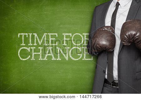 Time for change on blackboard with businessman wearing boxing gloves