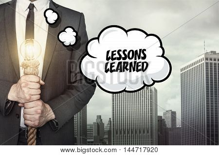 Lessons learned text on speech bubble with businessman holding lamp