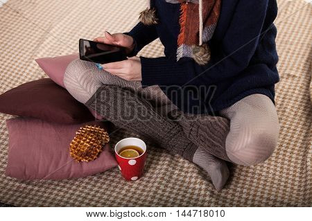 Young woman sitting on the floor and use the tablet.