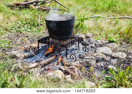 Cooking on a camp fire outdoors in summer sunny day