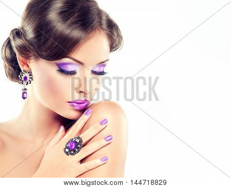 Model girl with a lilac make-up and manicure on nails. Woman jewelry with purple stones and  elegant hairstyle.