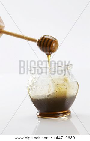 honey dipper with honey on the white background
