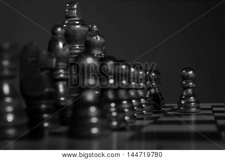 Black and white chess pieces on a wooden board