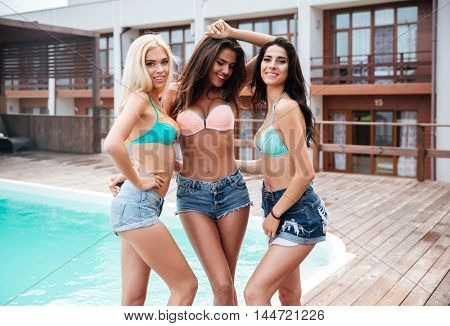 Three happy attractive young women standing near swimming pool