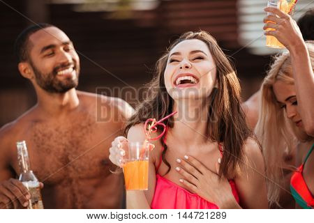 Portrait of a smiling young girl in bikini having fun with friends at pool party outdoors