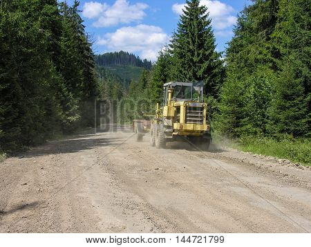Tractor trailer driving on dusty forest road in the Carpathian mountains