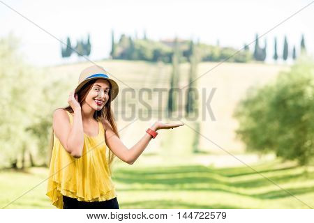 Young woman in hat and yellow shirt pointing on the beautiful Tuscan landscape in Italy.