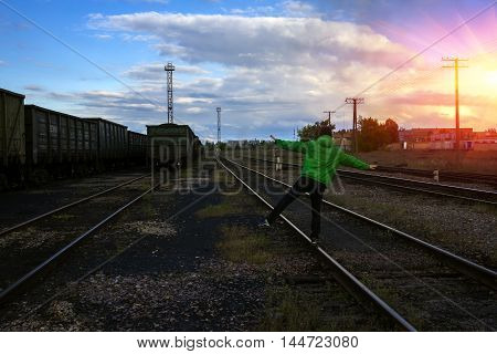 man travels on rails danger against the background of beautiful clouds.