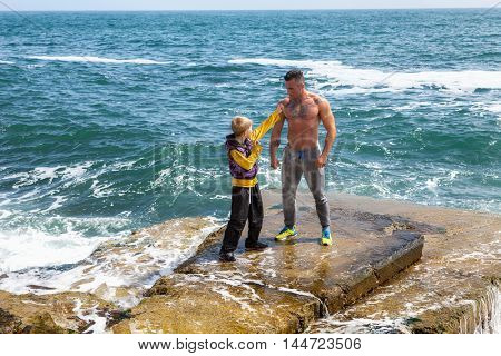 trainer with the pupil who is engaged in karate on the seashore