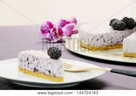A slice of violet mulberry cheesecahe on a white plate. Background: violet cheesecake and some flowers.