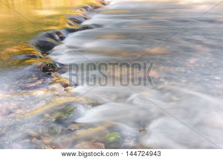 River flowing through golden and green foliage and rocks at sunlight, close up