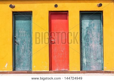 Three Colored Old Wooden Door And Yellow Wall