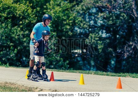 Senior teacher of roller skating with little boy practicing on class in the park