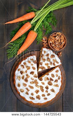 Carrot cake and fresh carrot on wooden table top view