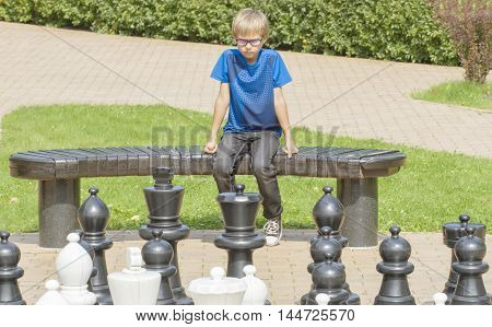 Outdoor chess game using life sized chess pieces and chess board. Concentrated child thinking about his next move sitting on a wooden bench.