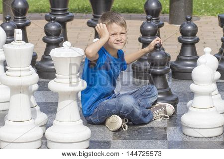 Outdoor chess game using life sized chess pieces and chess board. Boy thinking about his next move.