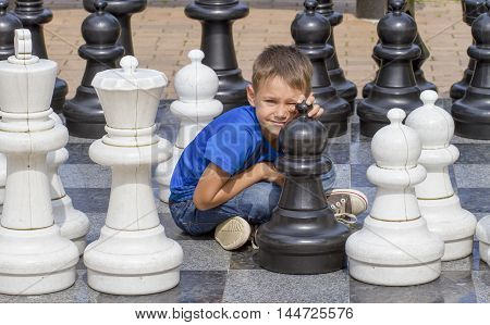 Smiling boy sitting on outdoor chess game board in the park
