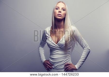 Fashion photo of a beautiful and confident young woman with blonde hair in a white dress. Natural retouched studio portrait.