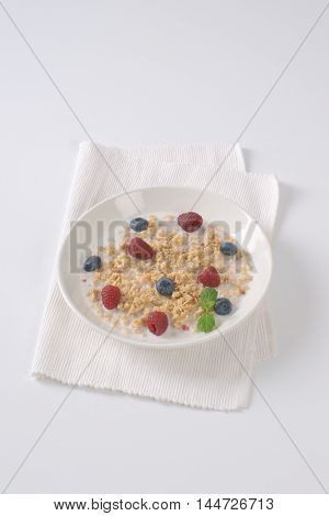 plate of granola with milk for healthy breakfast on white place mat