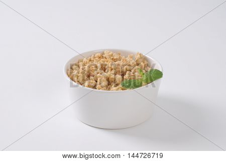 bowl of granola for healthy breakfast on off-white background with shadows