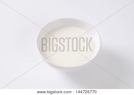 bowl of fresh milk on off-white background with shadows