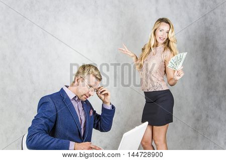 Businessman with laptop and secretary woman holding money on a gray background