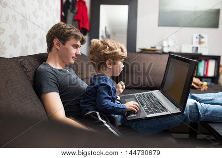 Father and son using laptop together on sofa at home.