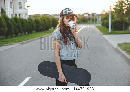 The girl with an active lifestyle starts with morning coffee and skate.