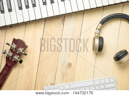 Computer Music production equipments with copy space. Music instruments on wooden table for background. Music writing equipment flat lay with copy space.