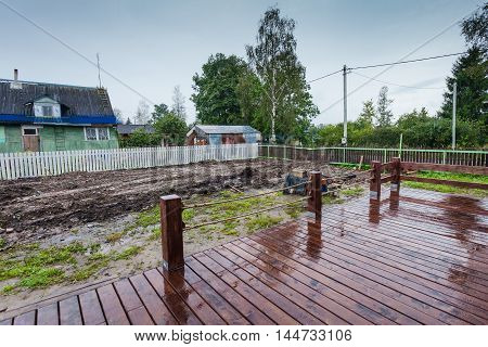 The building is under construction and wet and slippery wooden veranda