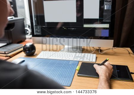 Young man at home using a computer, freelance developer or designer working.