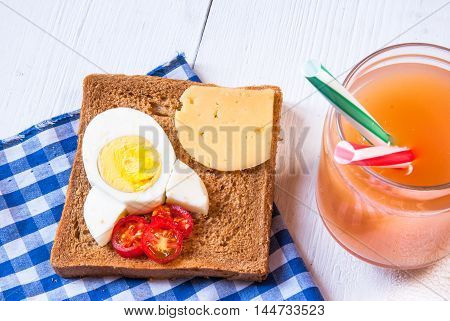 Funny breakfast for kid: sandwich with rocket cheese, eggs and tomatoes