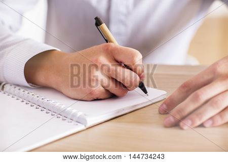 Closeup of businessman hands writing in spiral notepad on wooden desktop
